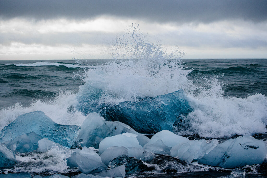 Icelands diamond beach in august. Waves crashing against tiny icebergs causing them to rock back and forth in the surf as the sunrise comes up behind the clouds. Traveling to Iceland and specifically diamond beach was always a life long dream.