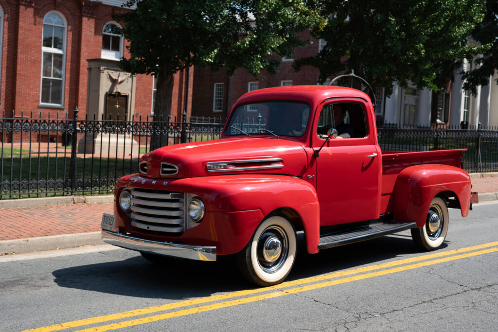 A bright red antique Ford truck rumbles down the street on white wall tires in old town Leesburg Virginia.