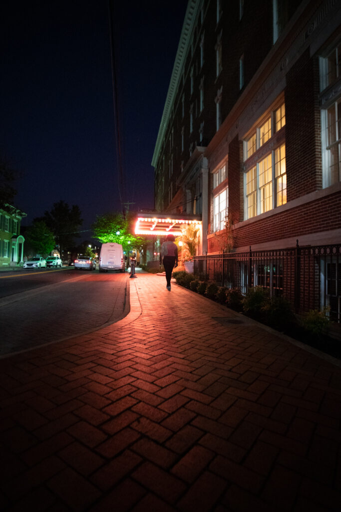 The vintage lights of a historic hotel in Winchester Virginia light an old brick walk way.