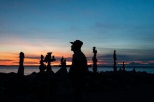 An artists stacks rocks on a Seattle beach in front of a beautiful sun setting over the pacific ocean.